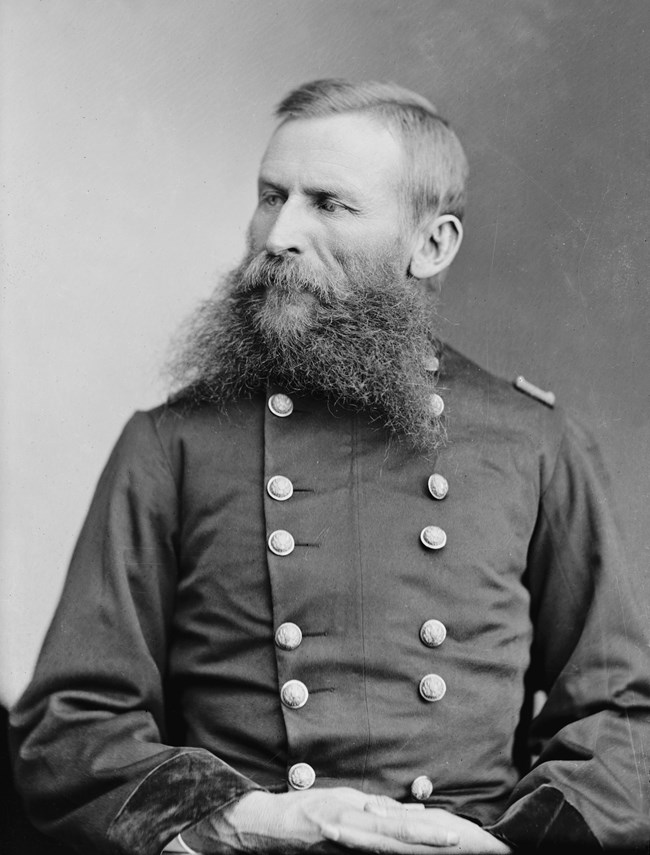 Black and white portrait of a man with a beard wearing a double-breasted coat.