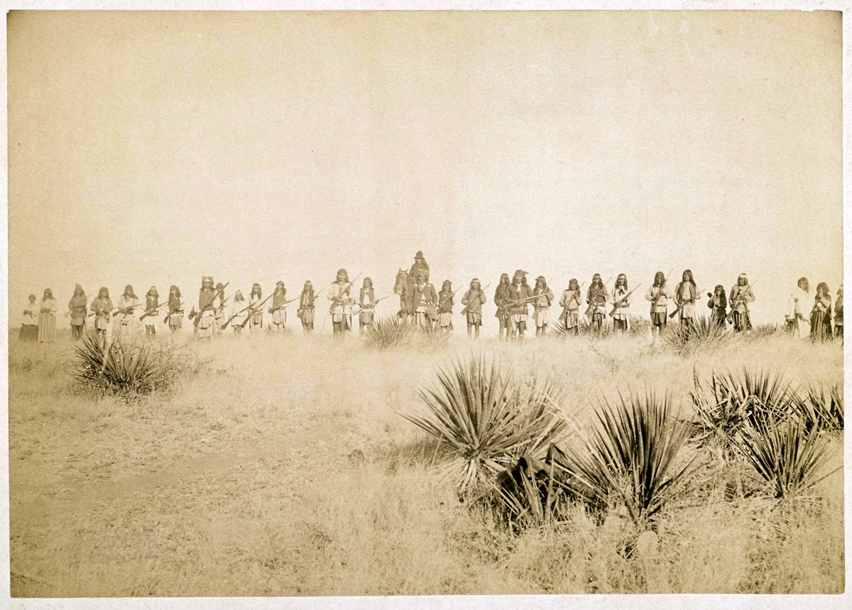 Sepia-tone photograph of line of warriors on foot, with one person on horseback. Agaves or yuccas and grasses in the foreground, and a clear sky in the background.
