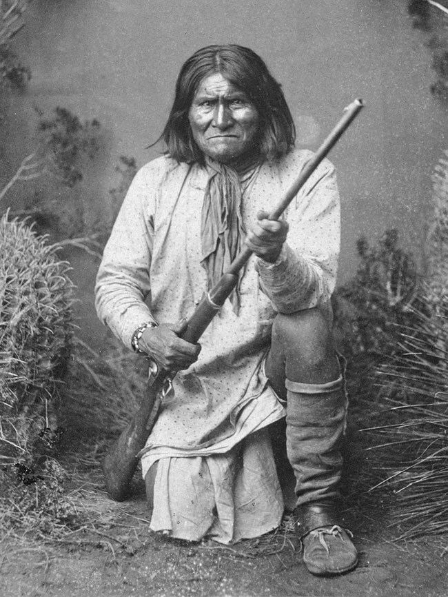 Black and white portrait of man with shoulder-length hair, kneeling, holding a rifle, and staring directly at the camera.