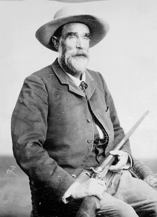 Black and white portrait of a seated man, holding a rifle. The man is wearing a hat and has a white beard.