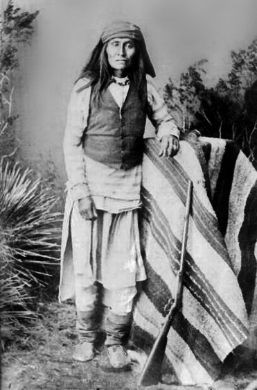 Black and white photograph of a long-haired man wearing pale clothes, a dark vest, and leaning against a table covered in a striped blanket, with a rifle leaning against the blanket.