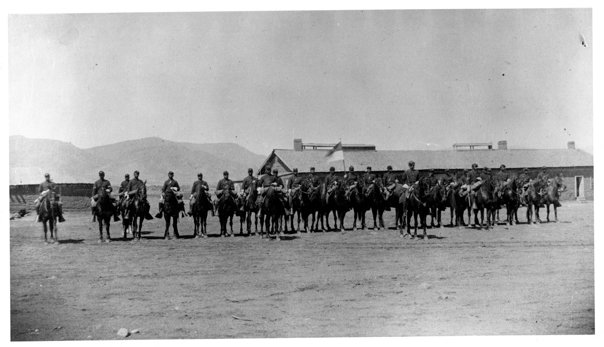 Black and white photo of African American soldiers on horses in front of building.