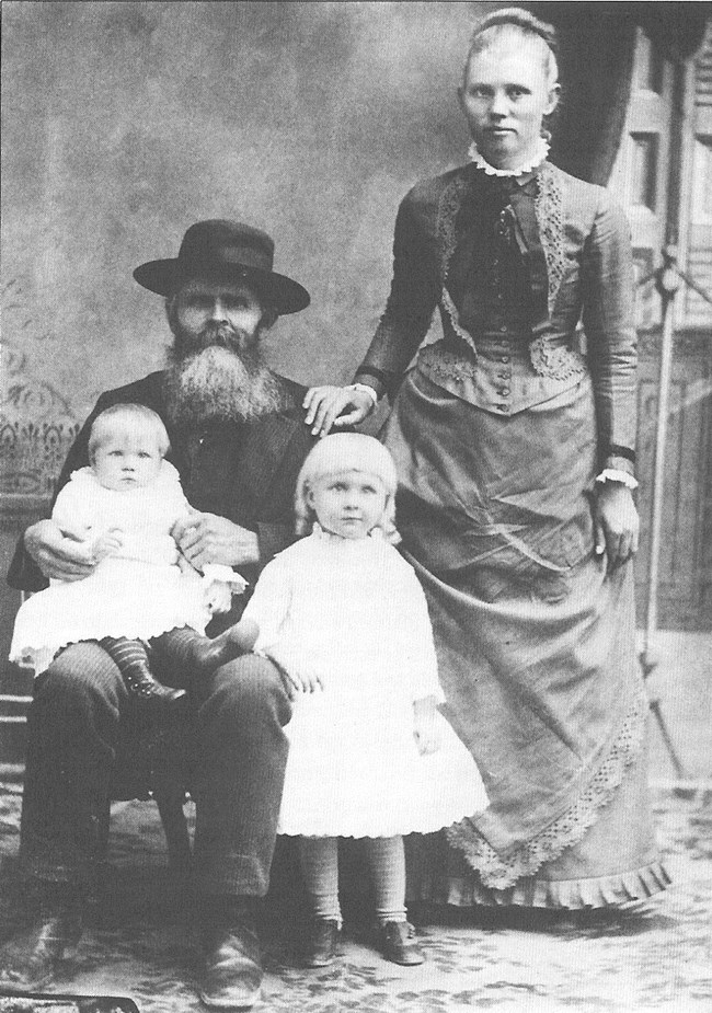 Black and white portrait of a man and woman and two young girls.