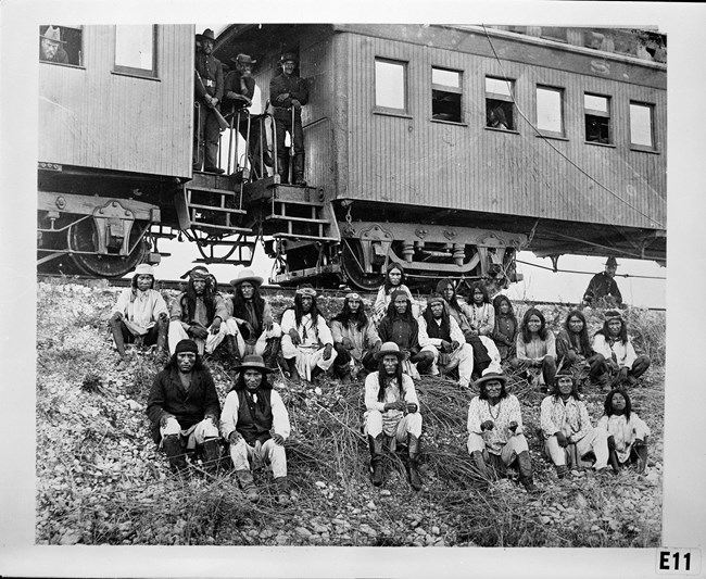 Group of men seated in front of train cars, guarded by Army soldiers standing on the train.