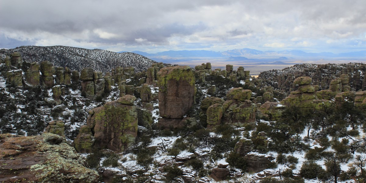 Photo of lots of rock formations covered in lichen, looking out towards a large valley.