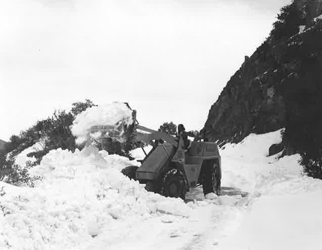 Black and white photo of snow removal on road using a backhoe.