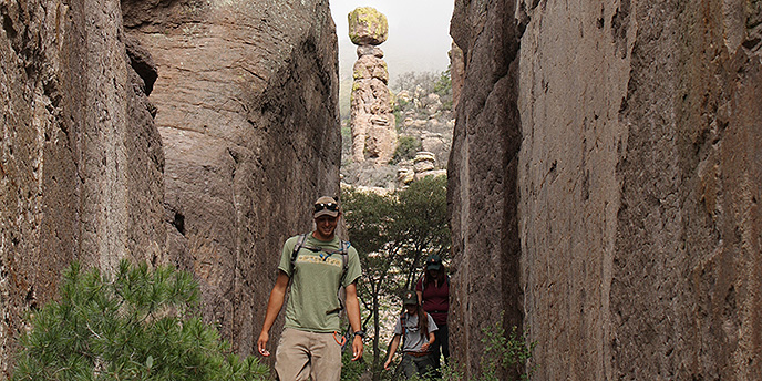 A hiker makes his way through a rock canyon