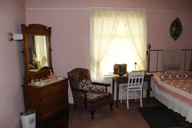 Pink bed room with vanity, table, chair, and bed.