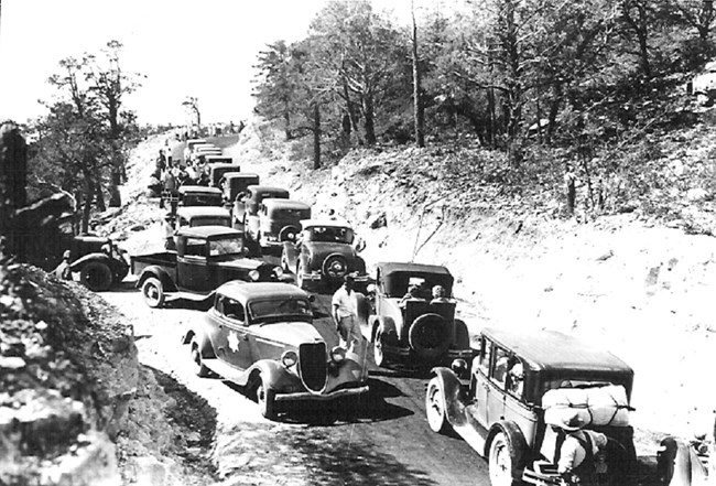 Black and white photo of narrow mountain road clogged with cars.
