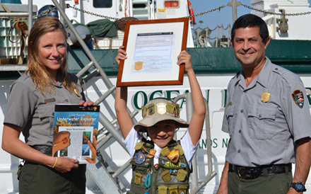 A young park visitor receiving a junior ranger award from two national park service rangers.