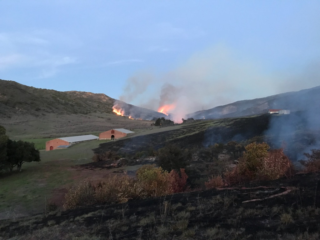 A wildifre burns through brush in the background. Structures are present in the foreground.
