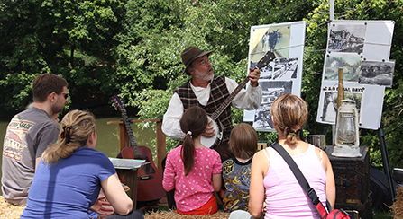 A banjo player performs to a few visitors along the towpath.