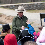 A park ranger talking with a school group along the towpath.