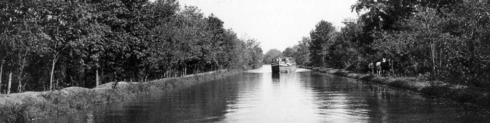 Coal Cargo Boat in the middle of the Canal being pulled by a mule team on the right hand side.