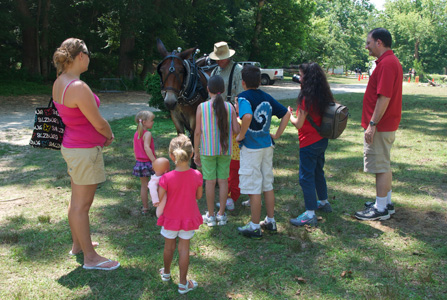 A ranger in costume and Eva the Mule meet visitors.