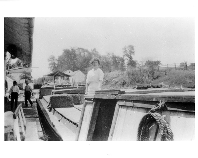 Historic Photo of a woman dtanding on a canal baot at four locks, with buildings and people walking in the background.