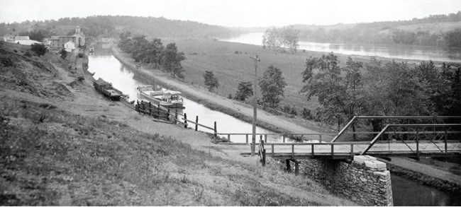 A view of the watered C&O Canal, with a canal boat in the water.