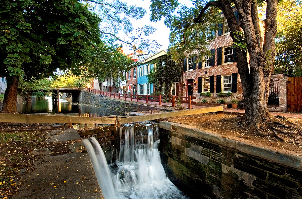 C&O Canal in Georgetown with water flowing through wooden structures called gates. Canal is surrounded by brick buildings.