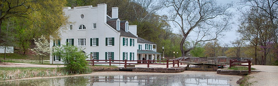 Water reflects the historic Great Falls Tavern