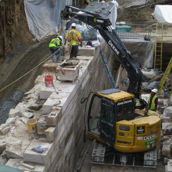 Two parallel light colored stone walls under construction.  Construction workers and equipment working on walls