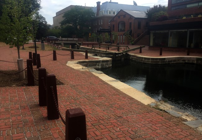 A canal lined with stone walls cuts through a brick plaza. There are dark colored, thick wooden post with chains around the plaza.