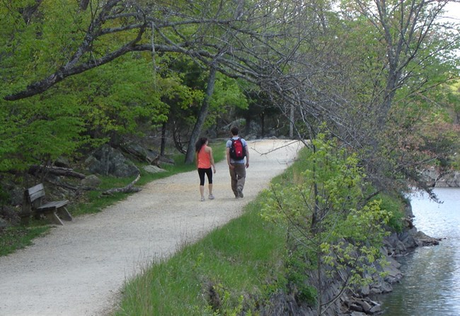 Two people walking along the towpath at Widewater.