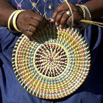 Hands of an African American woman sewing a colorful sweetgrass basket.