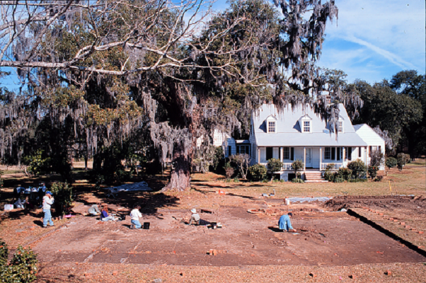 archaeologists working in front of historic coastal cottage