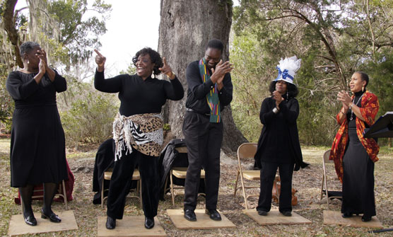 Five African Americans performing a cultural song and dance beneath a Live Oak tree.