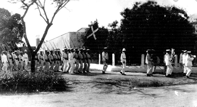 historic photo of Danish troops and military musicians marching in front of Fort Christiansvaern, ca. 1910