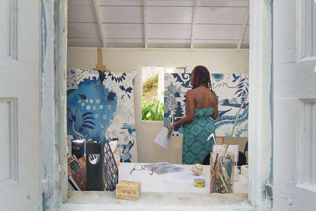 photograph of Crucian artist La Vaughn Belle painting in her studio