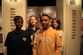 Four students stand in front of the exhibits and two columns with the words