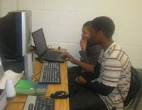 Two boys sit in front of a computer and work on their website projects.