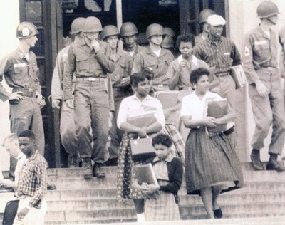 Members of the Little Rock Nine walking down the steps of Little Rock Central High School, escorted by soldiers,