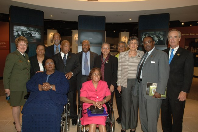 The Little Rock Nine stand in the park's new visitor center with NPS Director Mary Bomar, Interior Secretary Kempthorne, and Congressman Lewis.