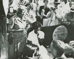 Elizabeth Eckford waits on a bus bench with her head in her hand as segregationist protestors surround her, yelling at her, September 4, 1957.