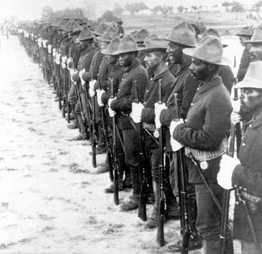 A long line of men standing with rifles in front of them