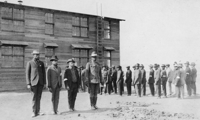 A group of men standing at attention in front of a large building