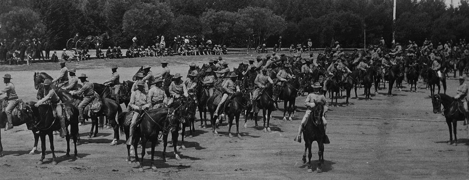 Several mounted soldiers on horses inside of a large dirt corral area.