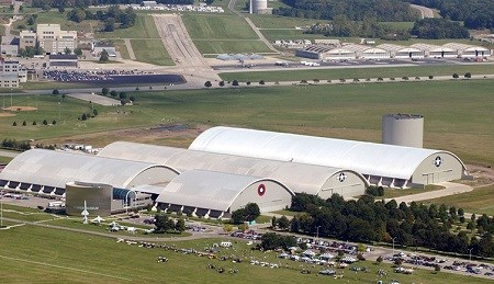 Three large gray buildings with curved roofs going towards the ground, sitting in a large green grass field and airplane runways in the background