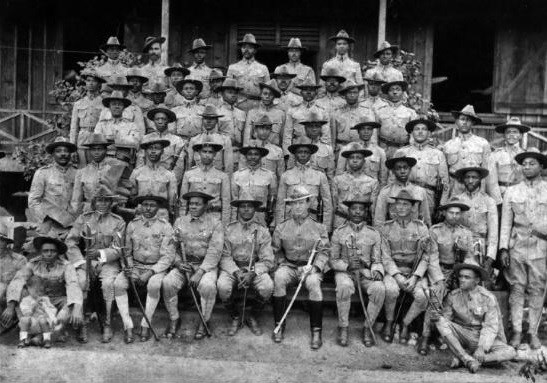 Several black Army soldiers standing and sitting while posing for a group portrait.
