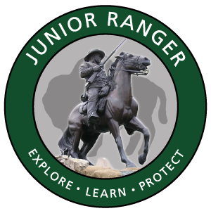 The park's Jr. Ranger logo showing a soldier on horseback holding a rifle surrounded by a green circle and a bison silhouette in the background.