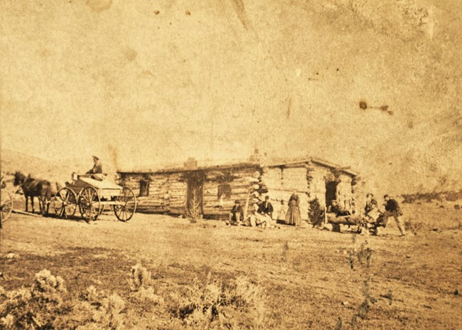 Historical Sepia photograph depicting a log building with several people sitting out front with a man sitting in a single horse drawn wagon.
