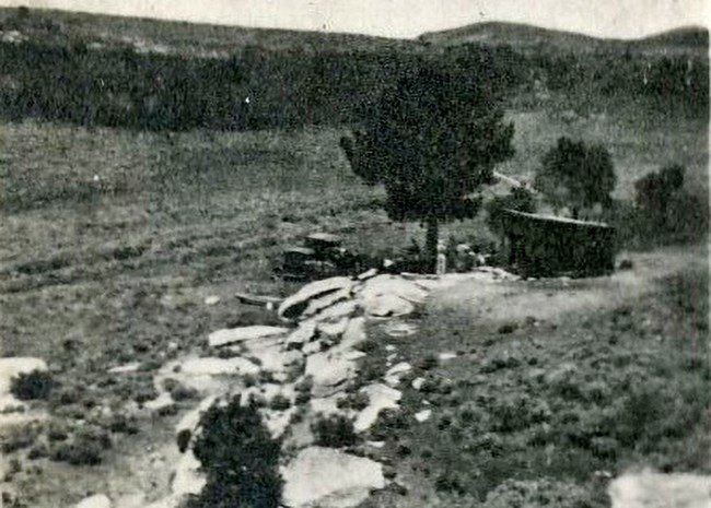 Grainy black and white photo where a building with an old truck parked out front is situated among rocks and juniper trees in what is now City of Rocks.