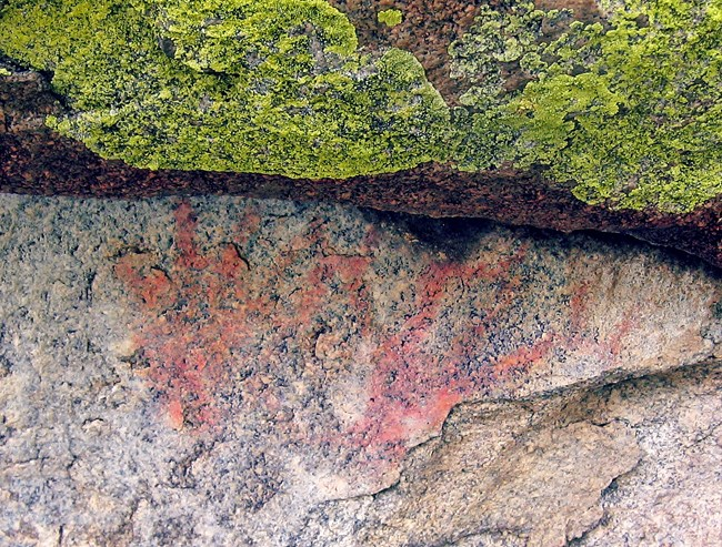Orange colored pictograph on granite thought to depict antlers, looks almost like two hand prints.