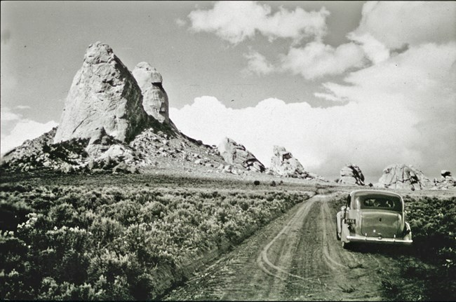 Black and white photo showing an old model car along a dirt road in front of towering granite spires.