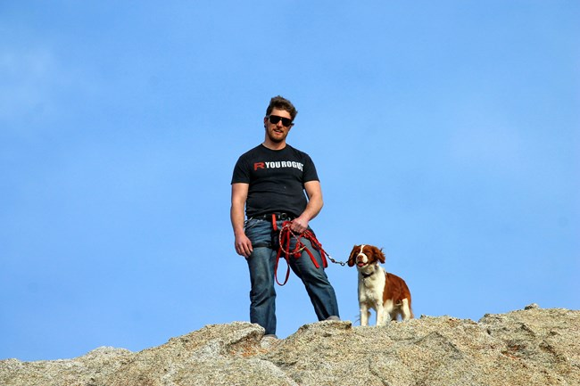 Hiker with dog on leash standing on top of a granite rock