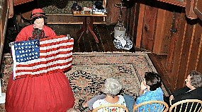 Actress Mary Ann Jung dressed as Clara Barton holds an American Flag during a performance of Clara Barton Red Cross Angel.