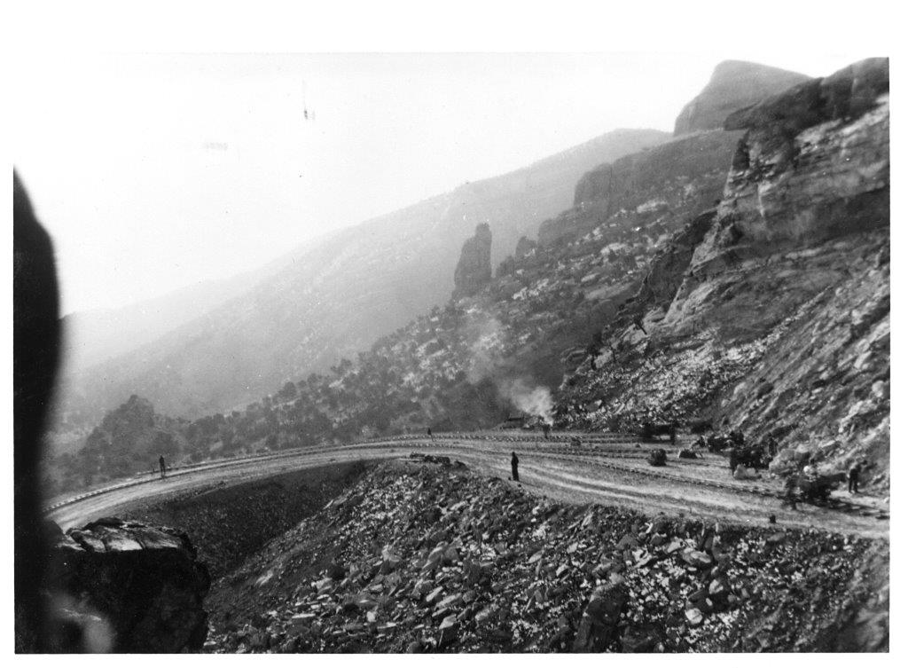 Black and white photograph of men working on a curved portion of Rim Rock Drive
