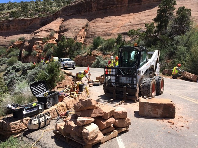 Equipment and pallets of large sandstone rock in the foreground await shaping and placement. In the background 6 staff members are working to install new rock to form walls along road.